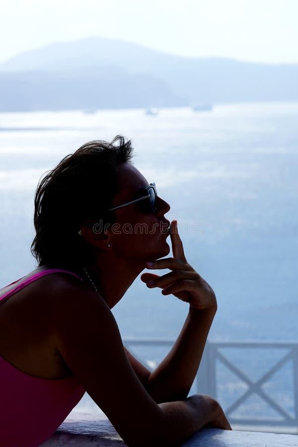 紫红色的礼服的妇女送一个亲吻到Oia的背景 库存图片