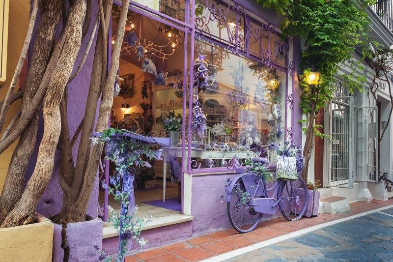 紫罗兰色纪念品店门面,装饰用紫罗兰色自行车在墙壁附近停放了 库存图片