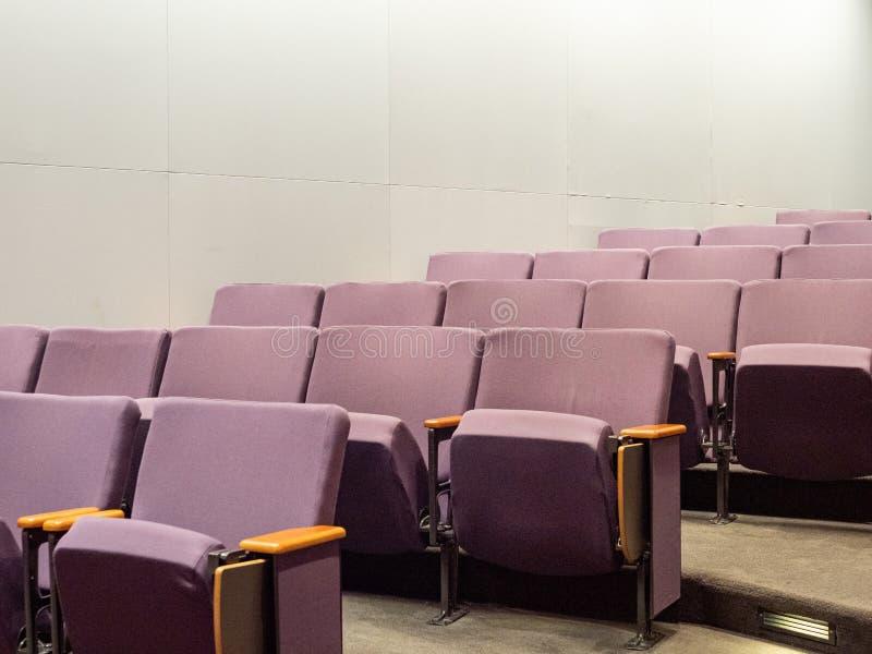紫色剧院样式椅子在空的干净的小观众席 库存照片