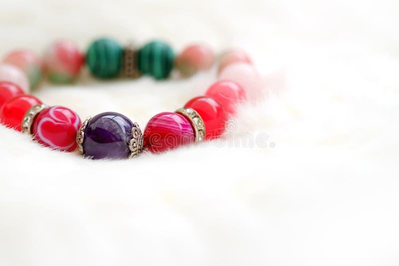 紫色和桃红色在白色羊毛背景的口气幸运的玛瑙石头 免版税库存照片