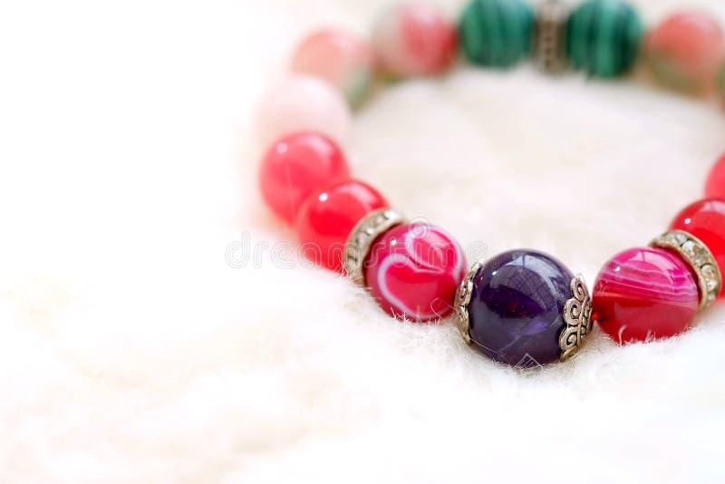 紫色和桃红色在白色羊毛背景的口气幸运的玛瑙石头 库存照片