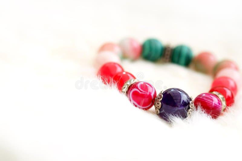 紫色和桃红色在白色羊毛背景的口气幸运的玛瑙石头 免版税库存图片