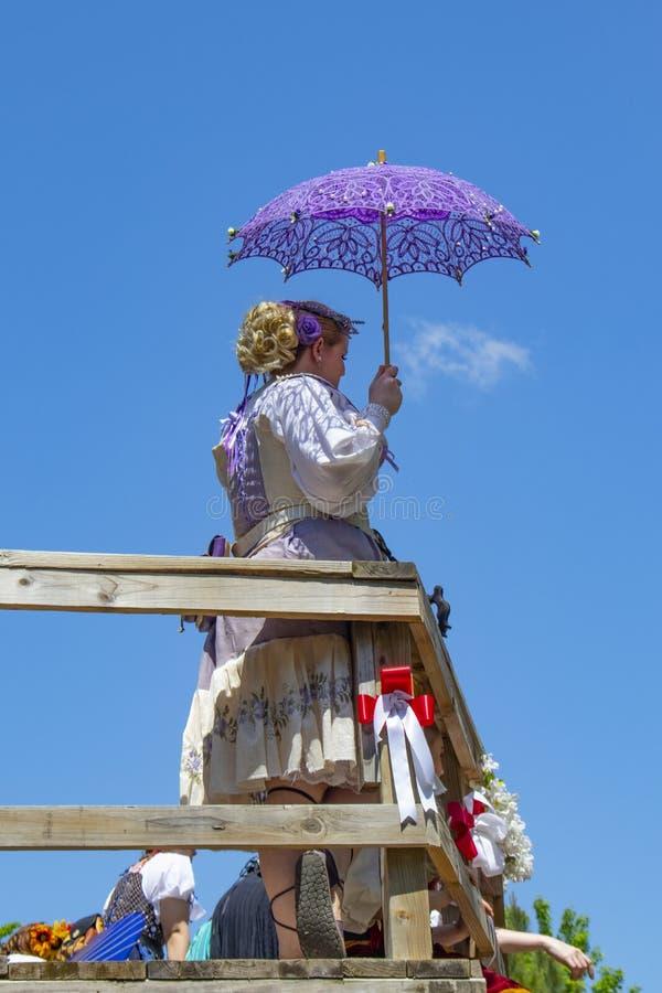紫色和白色服装的妇女有紫色有花边的反对非常bue天空的遮阳伞支持的栏杆的在俄克拉何马新生Festi 库存照片