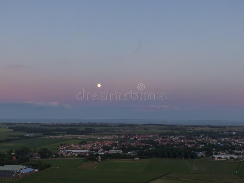 紫色天空的空中图象在日落以后的与在平的草甸土地、海和村庄的满月在荷兰海岛特塞尔上 免版税库存图片