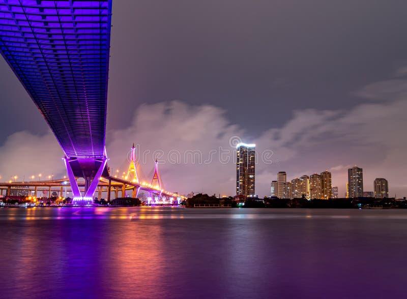 紫色带领了光在河的桥梁下在天空的一阴天 普密蓬桥梁,萨穆特Prakan,泰国 免版税库存图片