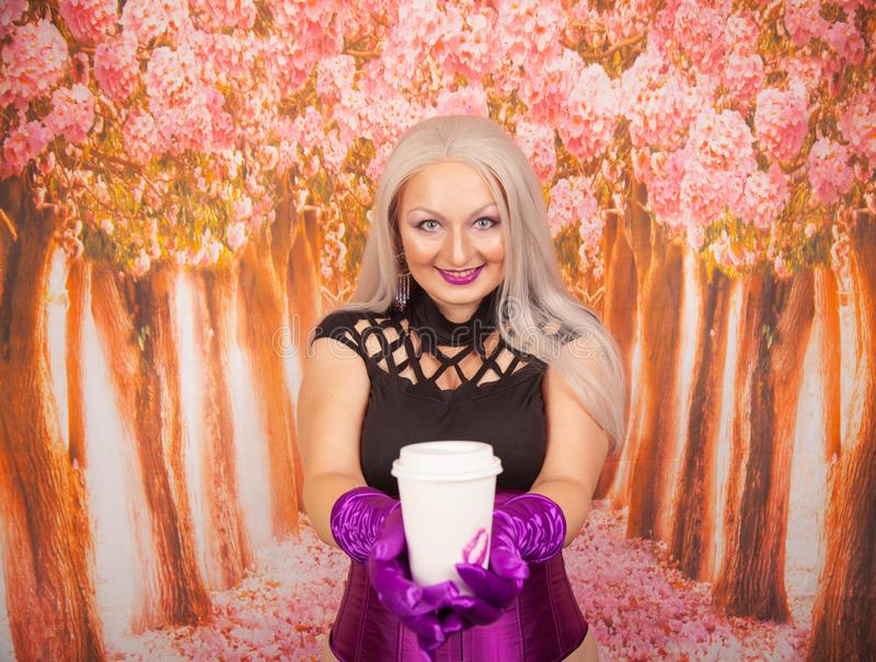 紫色束腰的迷人的肥满白肤金发的妇女有长的手套的拿着一纸杯与她的唇膏k标记的外带的咖啡  免版税库存照片