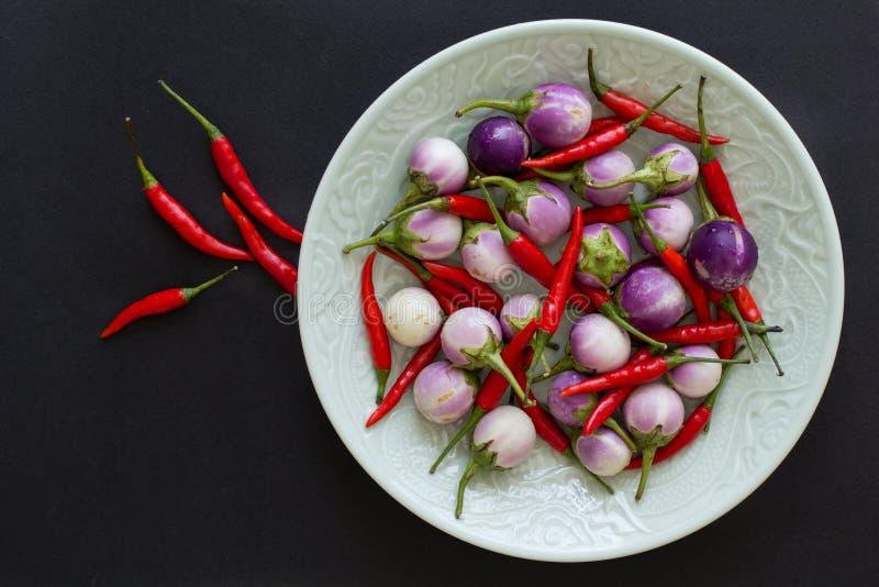 紫色泰国茄子和辣椒在一块绿色板材和附近在黑背景 E 库存照片