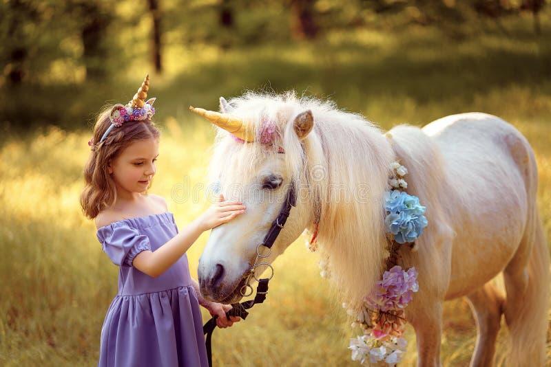 紫色礼服的女孩有一只独角兽的花圈的在头发拥抱的和亲吻的白色独角兽的 E ?? 免版税库存照片