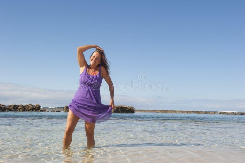 紫色礼服的性感的成熟妇女 库存图片