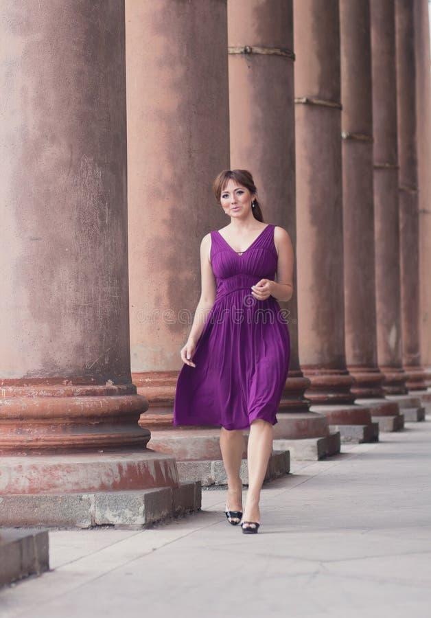 紫色礼服的美丽的妇女在专栏附近 库存图片