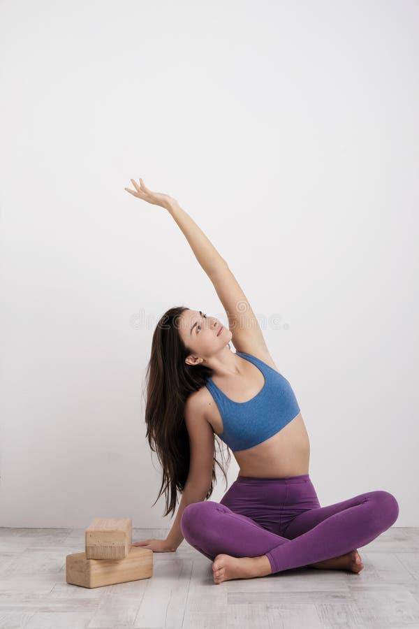 紫色绑腿和体育T恤杉的年轻深色的妇女做在地板上的锻炼 在块的平衡和 图库摄影