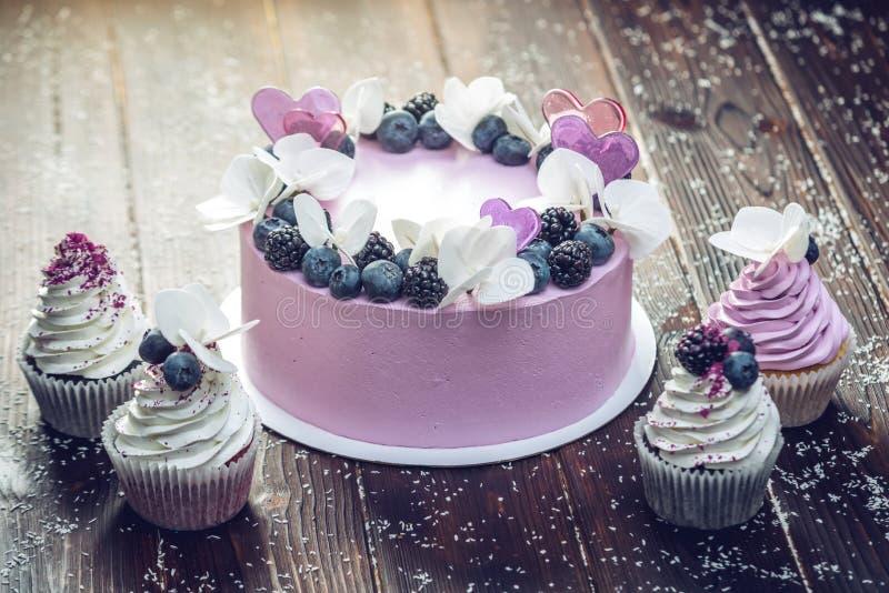 紫色美丽的蛋糕装饰用莓果、黑莓和蓝莓在上面用杯形蛋糕在欢乐桌上 图库摄影