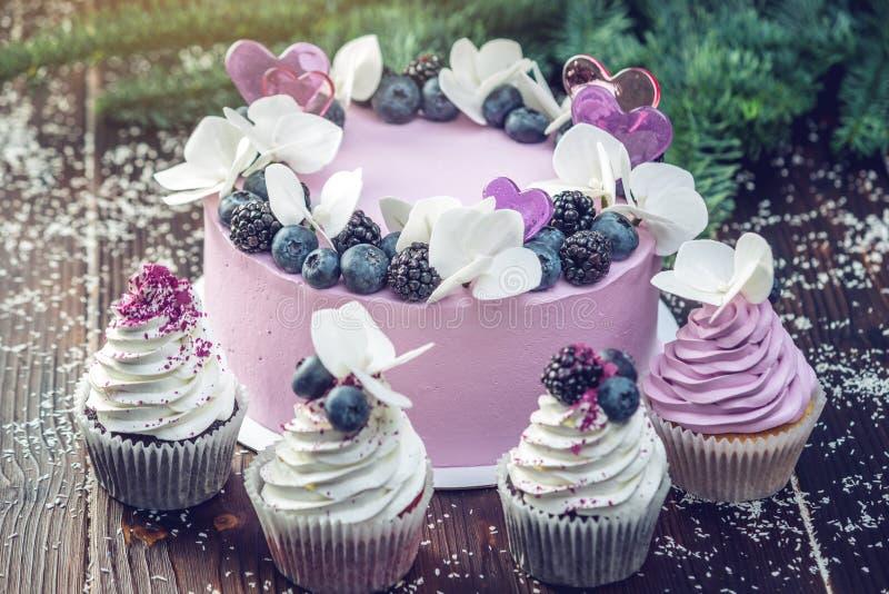 紫色美丽的蛋糕装饰用莓果、黑莓和蓝莓在上面用杯形蛋糕在欢乐桌上 库存图片