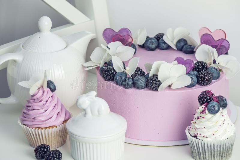 紫色美丽的蛋糕装饰用莓果、黑莓和蓝莓在上面用杯形蛋糕在欢乐桌上 免版税库存图片