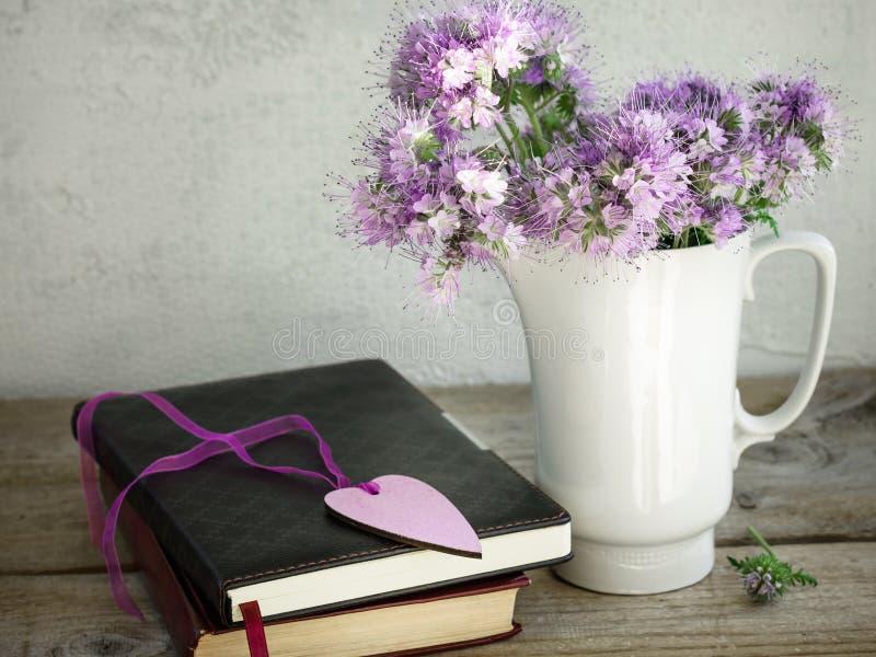 紫色花,在一张老木桌上的书花束  免版税库存照片