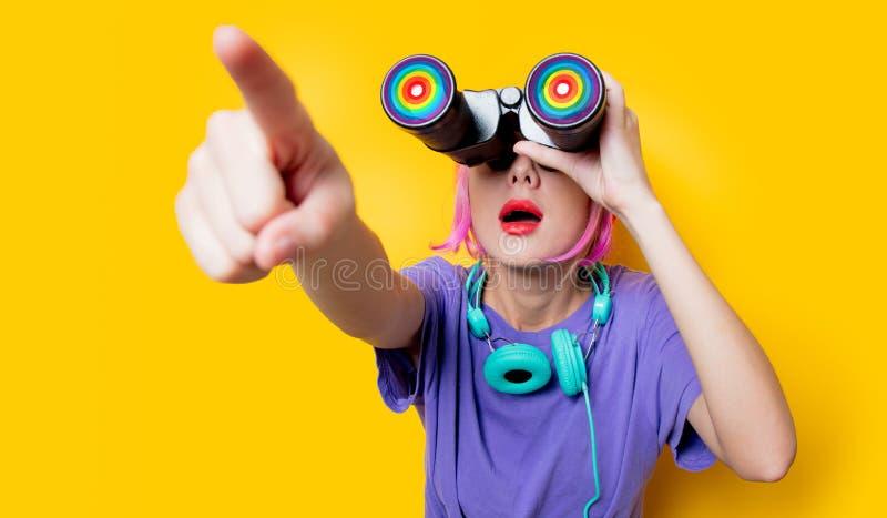 紫色衣裳的年轻样式女孩有双筒望远镜的 库存照片