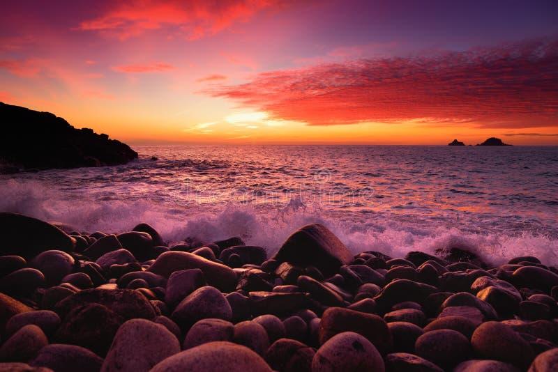 紫色设色了打破在一个多岩石的海滩的波浪在Porth Nanven的日落在康沃尔郡,英国轻便小床谷  库存图片
