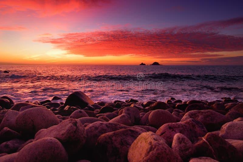 紫色设色了打破在一个多岩石的海滩的波浪在Porth Nanven的日落在康沃尔郡,英国轻便小床谷  免版税库存图片