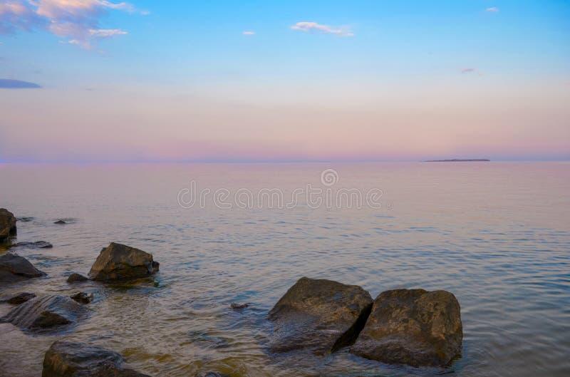 紫色黄昏 在风平浪静的美丽的云彩 在海的桃红色日落 免版税库存照片