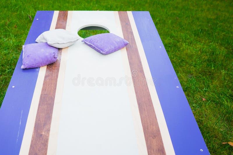 紫色Cornhole辎重袋抛比赛 免版税库存照片