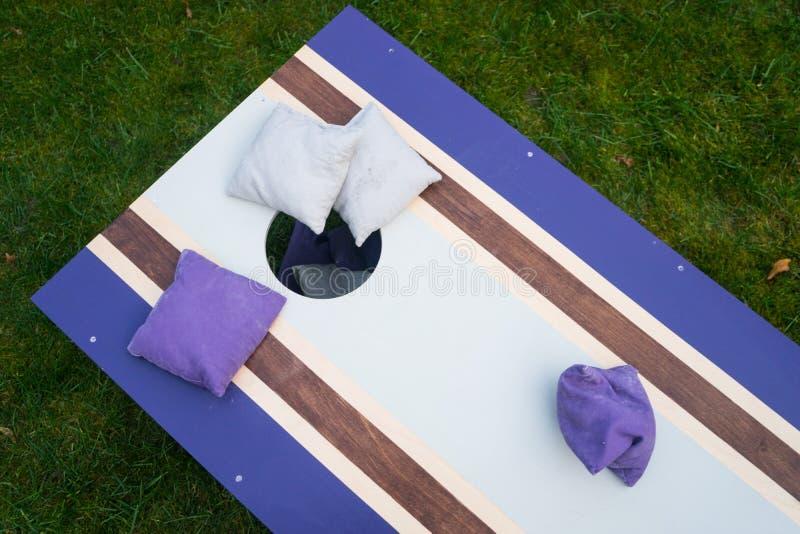 紫色Cornhole辎重袋抛比赛 图库摄影