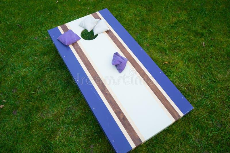 紫色Cornhole辎重袋抛比赛 免版税库存图片