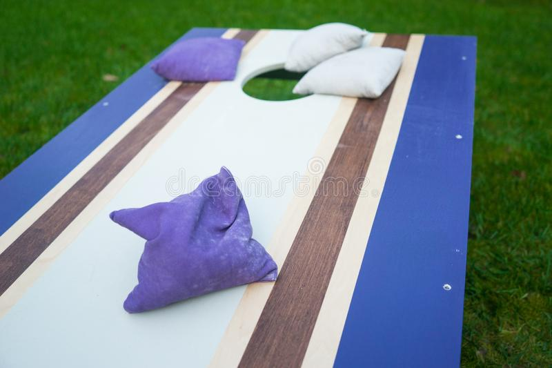 紫色Cornhole辎重袋抛比赛 免版税图库摄影