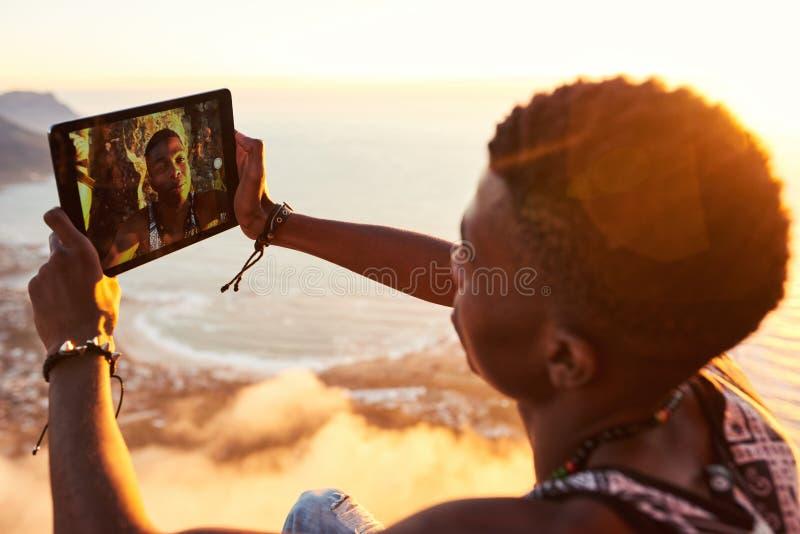 繁忙年轻的黑人采取与片剂的一selfie 免版税库存图片