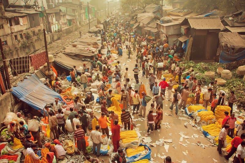 繁忙的人民买的花人群在Mullik Ghat在印地安街道上的花市场上 免版税图库摄影