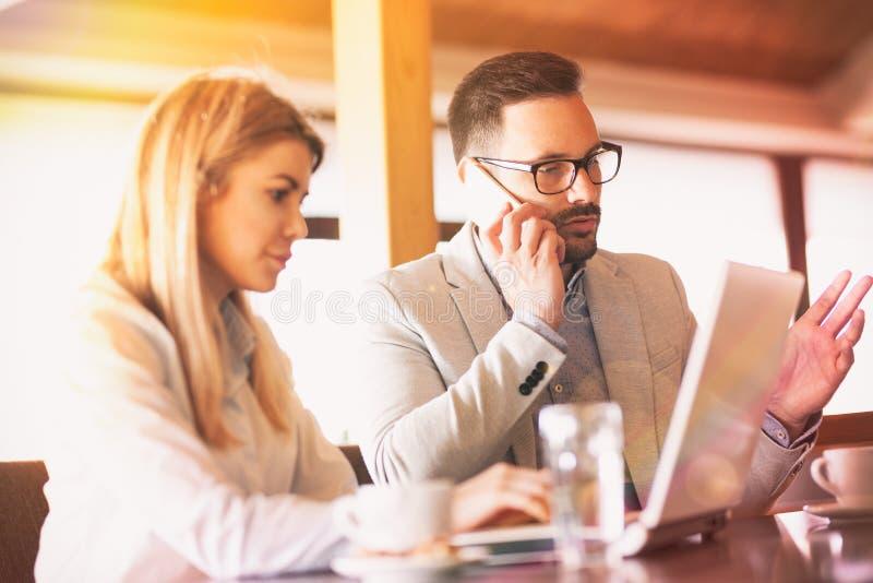 繁忙的企业同事研究膝上型计算机和谈话在电话 库存图片
