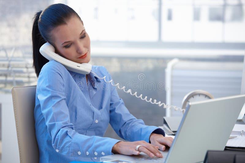 繁忙的女勤杂工与电话和计算机一起使用 免版税库存图片