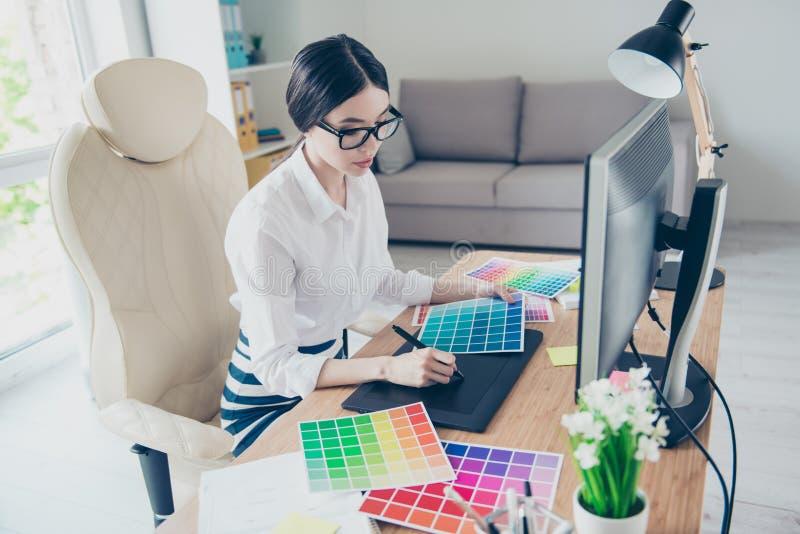 繁忙的年轻亚裔图表设计师画某事在graphi 图库摄影
