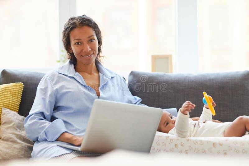 繁忙的母亲与膝上型计算机一起使用 免版税库存图片