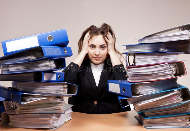 繁忙的经理 有堆的女实业家文件夹和文件 免版税库存图片
