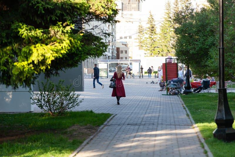 红伯根地长的礼服的一个女孩通过一个公园在市中心在树荫,一明亮的好日子下走与绿色树 免版税库存图片