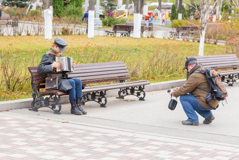 红军委员的军服的一年轻人在内战期间坐长凳并且播放泛音 库存图片