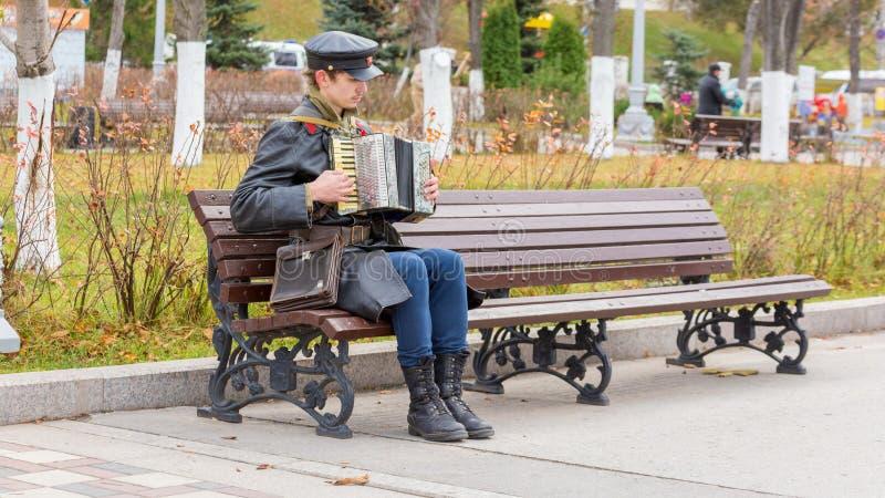 红军委员的军服的一年轻人在内战期间坐长凳并且播放泛音 库存照片