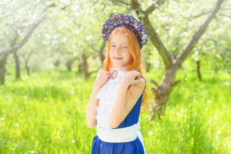 红发女孩在一个晴朗的庭院里 库存照片