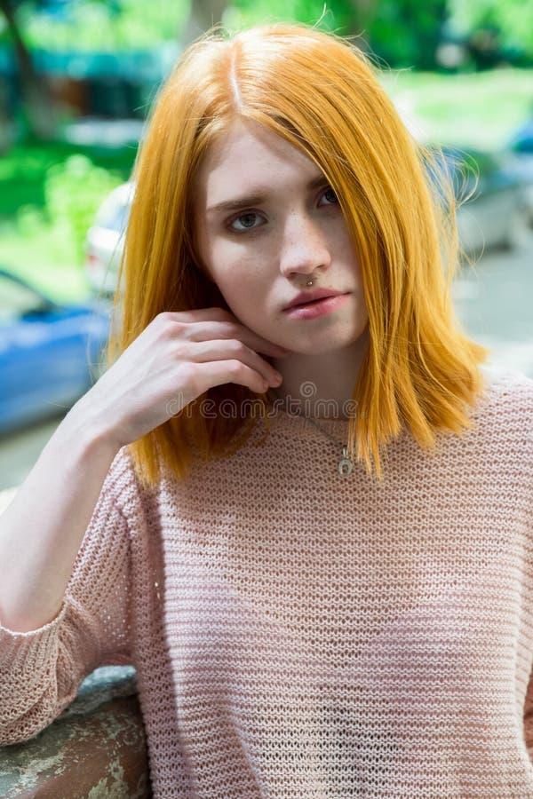 红发女孩在石柱子附近站立 库存照片