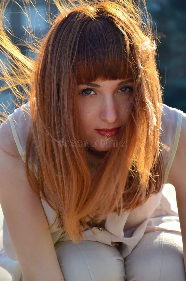 红发女孩,在风的子线画象  免版税库存照片