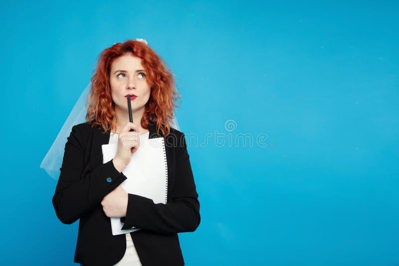 红发女孩,新娘拿着笔记的一个笔记本与沉思神色,计划她的事务 在蓝色的孤立 免版税库存照片