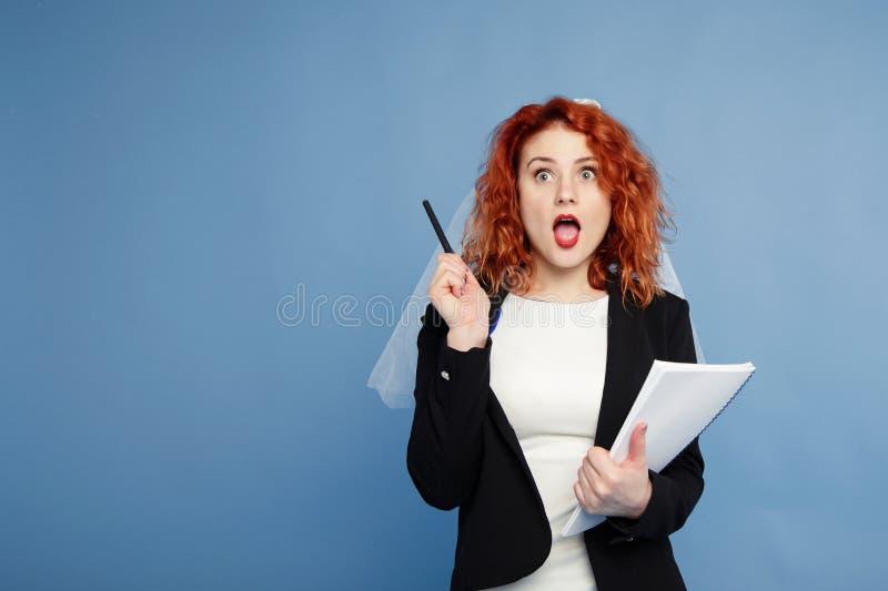 红发女孩,新娘拿着笔记的一个笔记本与沉思神色,计划她的事务 在蓝色的孤立 免版税图库摄影