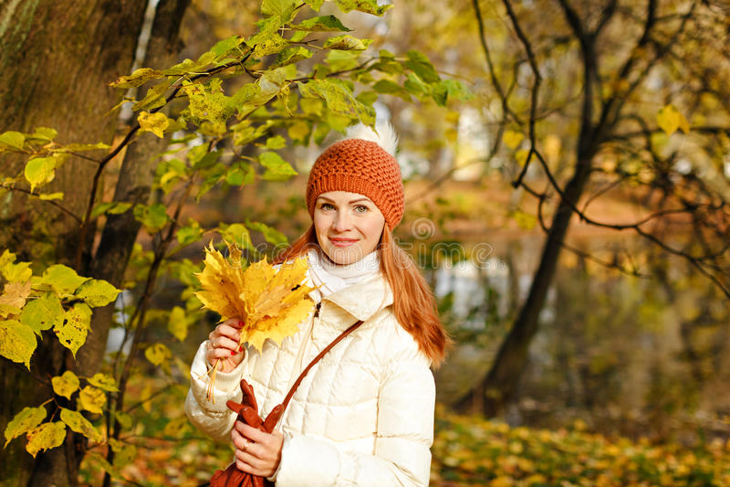 红发妇女微笑的愉快的秋天 免版税库存照片
