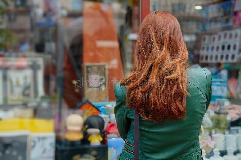 红发妇女看一个商店窗口 免版税库存照片