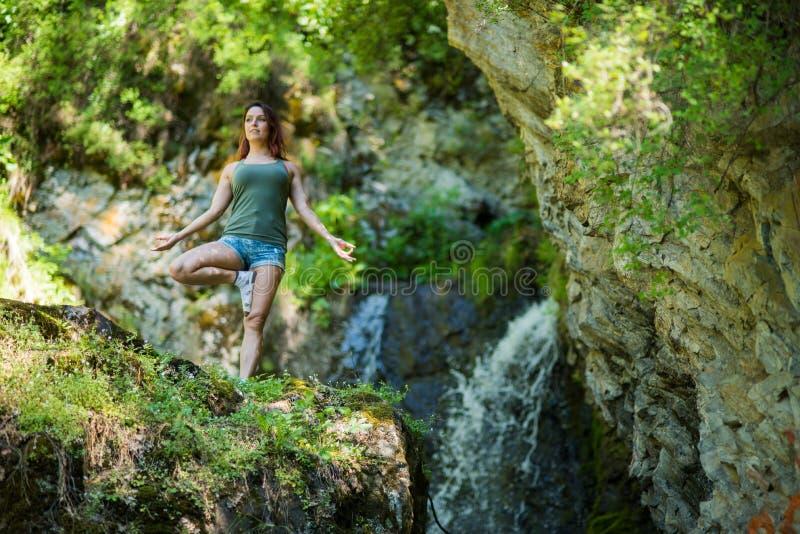 红发妇女简而言之做瑜伽的在瀑布 r 免版税库存照片