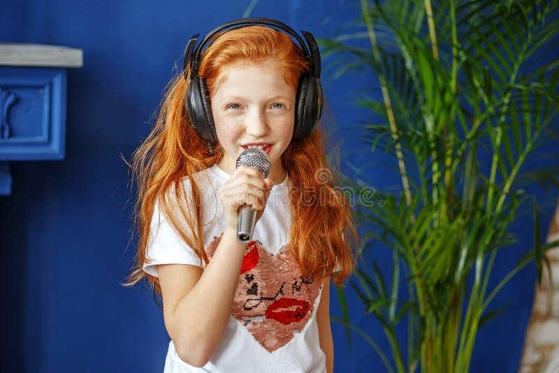 红发小女孩唱歌曲 概念是童年, 免版税库存照片