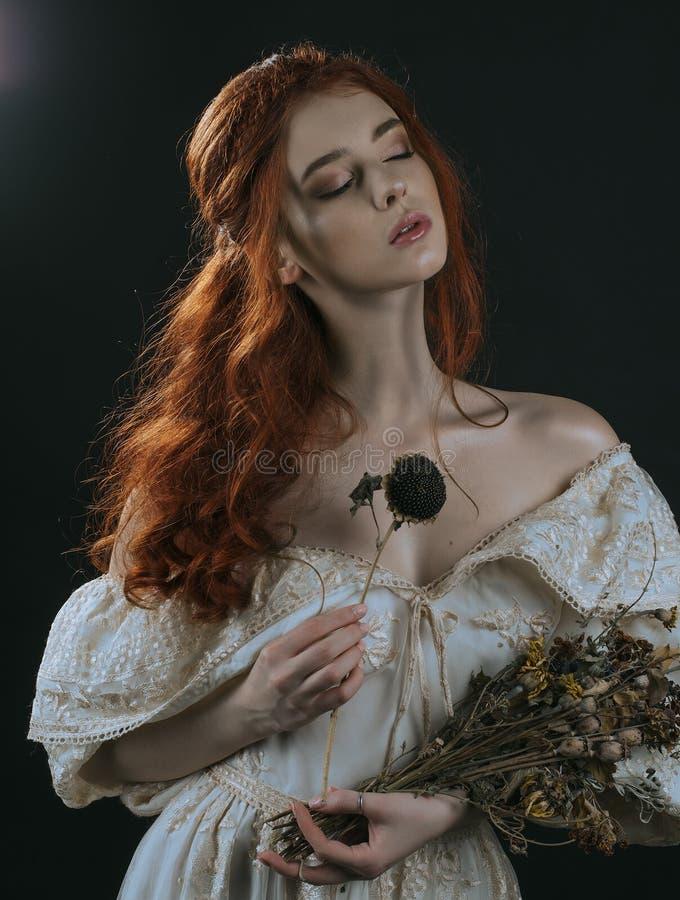 红发少妇的画象葡萄酒金礼服的有干燥花束的在手上在黑背景 一位公主 神仙 库存照片