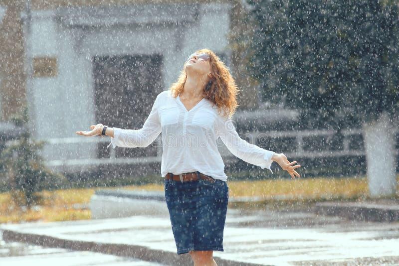 红发愉快的妇女在雨中 库存照片