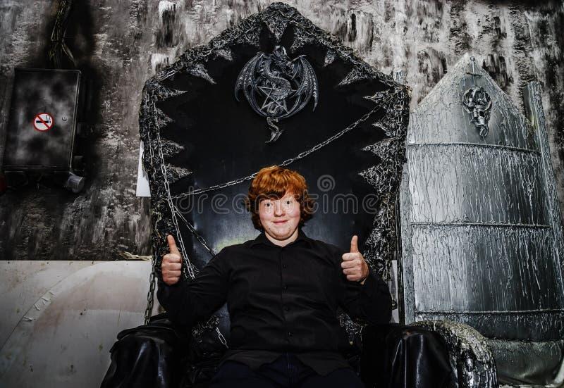 红发男孩坐不可思议的王位 免版税库存图片