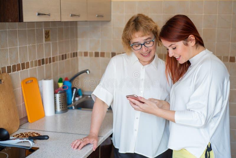 红发的女人教一位年迈的母亲如何使用智能手机 母亲和成年女儿穿白色衬衫 免版税库存照片